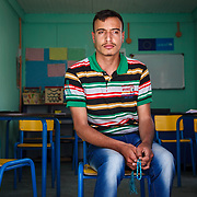 Alaa, 18, and his family have been living in Zaatari for almost three years, since the camp first opened, after fleeing Daraa. Alaa is holding prayer beads, a gift from his best friend before he left Syria.<br /> <br /> Alaa is sitting in a Mercy Corps resource room where he receives one-on-one instruction as a participant in Mercy Corps' inclusive education project for students with disabilities. He has cerebral palsy and was not enrolled in school until Mercy Corps met him and showed him that attending school can be a good thing. Zaatari camp for Syrian refugees, Jordan, May 2015.