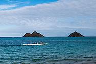 Outrigger canoe team off Lanikai Beach, Kailua Bay, Oahu, Hawaii. Mokulua Islands in background