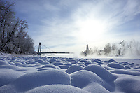 Winter landscape photography on the shore of the Bow River with the Southland Pedestrian Bridge in the background. It was an extremely cold day and a beautiful layer of ice fog blanketed the river.<br /> <br /> ©2017, Sean Phillips<br /> http://www.RiverwoodPhotography.com