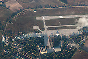EXCLUSIVE<br /> Vanishing Chernobyl: Aerial photos show how devastated town in radiation disaster zone is being reclaimed by nature<br /> <br /> Devastated by the worst nuclear disaster in history, Chernobyl is now a barren ghost town slowly being forgotten.<br /> These astonishing aerial photographs of the former power plant and the neighbouring city of Pripyat show how they are becoming hidden from view as the surrounding forest closes in.<br /> Following the disaster - which occurred during a systems test on April 26, 1986 -  the Ukrainian government evacuated 350,000 residents from Chernobyl and Pripyat.<br /> <br /> An exclusion zone covering an area of more than 1,000sq miles around the abandoned plant was created to protect people from the effects of any lingering radiation.<br /> These pictures of the zone - taken from a height of 10,000 metres, show how after 27 years of remaining largely uninhabitable, the surrounding Red Forest is slowly reclaiming the plant and the city. <br /> <br /> <br /> Pripyat was founded in 1970 for the Chernobyl Nuclear Power Plant and grew to a population of 49,360 before it was evacuated a few days after the disaster. The pictures, as reported by EnglishRussia.com, show its residential buildings spurting out from the thick woodland below.<br /> The secret Duga-1 complex can also be seen among the dense woodland. The radar system could detect launches of a potential enemy in North America. But despite its hi-tech capabilities, it is now left to ruin.<br /> <br /> <br /> The accident on April  26,1986, created a huge explosion and fire which released large quantities of radioactive particles into the atmosphere, spreading over western USSR and Europe.<br /> Although tens of thousands of people evacuated the area, a few residents refused to leave. A handful of older residents moved back to be close to family graves.<br /> Tourists may obtain day passes, and some workers who are rebuilding parts of the site are allowed in for limited hours only each month.  Scientists say the area will not be safe to live in for another 20,000