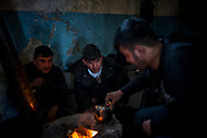 Migrants from Afghanistan preparing tea on a stove made from an old barrel in Belgrade train station makeshif camp. March 17th, 2017, Belgrade, Serbia. Federico Scoppa
