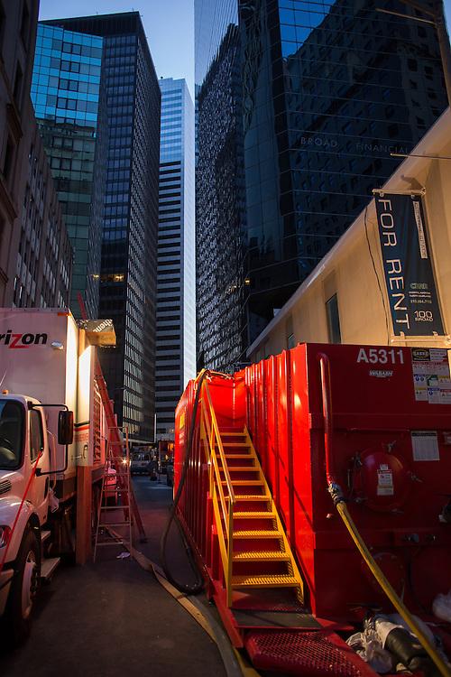 Hazardous waste conatiners and Verizon trucks block the street.