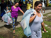 """22 JANUARY 2018 - GUINOBATAN, ALBAY, PHILIPPINES: Women in an evacuation center in Guinobatan pick up relief supplies at the shelter. Several communities in Guinobatan were hit ash falls from the eruptions of the Mayon volcano and many people wore face masks to protect themselves from the ash. There were a series of eruptions on the Mayon volcano near Legazpi Monday. The eruptions started Sunday night and continued through the day. At about midday the volcano sent a plume of ash and smoke towering over Camalig, the largest municipality near the volcano. The Philippine Institute of Volcanology and Seismology (PHIVOLCS) extended the six kilometer danger zone to eight kilometers and raised the alert level from three to four. This is the first time the alert level has been at four since 2009. A level four alert means a """"Hazardous Eruption is Imminent"""" and there is """"intense unrest"""" in the volcano. The Mayon volcano is the most active volcano in the Philippines. Sunday and Monday's eruptions caused ash falls in several communities but there were no known injuries.    PHOTO BY JACK KURTZ"""
