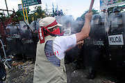 10 SEPTEMBER 2003 - CANCUN, QUINTANA ROO, MEXICO: Anti-globalization protestors battle Mexican riot police at the fence separating the downtown area from the hotel zone in Cancun, Quintana Roo, Mexico during a protest against the WTO. Tens of thousands of people opposed to the WTO have come to this Mexican resort city to protest the 5th Ministerial meeting of the World Trade Organization. The WTO meetings are taking place in the hotel zone of Cancun, about 10 miles from the protestors.  PHOTO BY JACK KURTZ