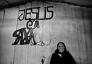 """The portrait of a gypsy woman, resting against the wall of the church of their community.<br /> The gipsies call it """"the Cult"""", it is a kind of pact that they get together twice a week in a common hut to pray for good and exorcise the evil. Inside the hut there´s a heavy atmosphere and things seem to be a blend of fantasy and reality. Tens of gipsies form a circle of screams and cries and you can hear a mix of prays, complains, desperation and guilt. A gipsie women faints on the floor almost like she has been exorcised and she had a demon inside her, slowly with the help of the others she recovers.<br /> The truth is that the cult is a way that gipsies chose to express themselves, something that is very much theirs, just like the sound of the gipsies guitars, shows something very real, the suffering of their spirits."""