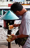 Worshipper at  Siew San Teng temple burning paper money.