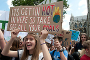 School Climate Strike, London, England, UK. A girl holds a handpainted sign saying Its getting hot in here so take off all your coals.
