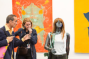 """New York, NY - 6 May 2016. Frieze New York art fair. A man and a woman examine one of a pair of sculptures, titled """"Les guérillieres"""", by Mai-Thu Perret in the David Kordansky Gallery."""