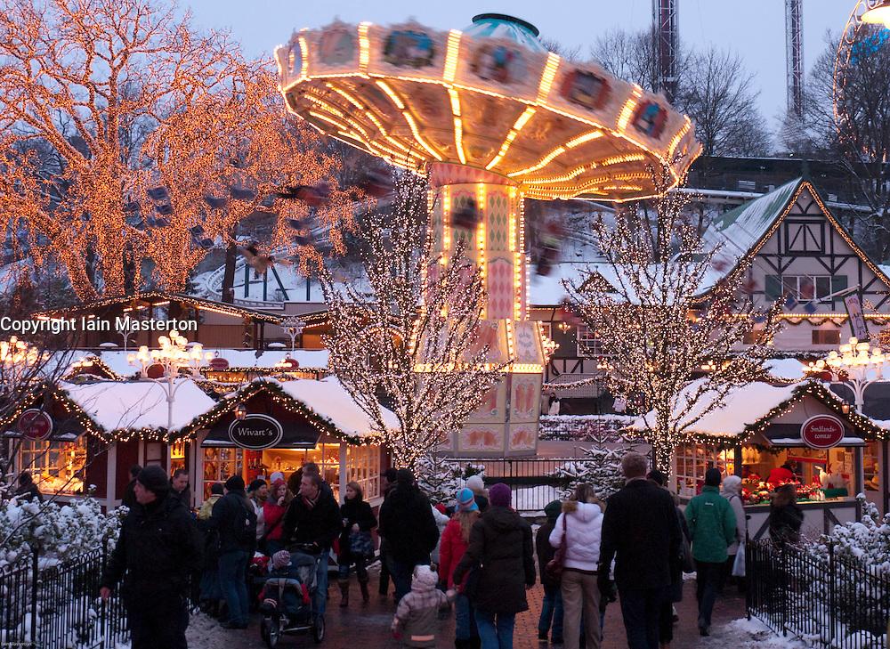Funfair and small wooden craft shops at dusk at Christmas market in Liseberg amusement park in Gothenburg Sweden
