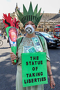 A demonstrator wearing a Statue of Liberty costume with a photo of US President Donald Trump on its torch, stands at Parliament Square during an Extinction Rebellion climate change protest in London, Tuesday, Sept 1, 2020. (VXP Photo/ Vudi Xhymshiti)