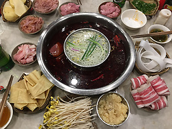 June 7, 2017 - Chongqing, Chongqing, China - Chongqing, CHINA-June 7 2017: (EDITORIAL USE ONLY. CHINA OUT) Raw foods of Chongqing hotpot are ready to be cooked and the hot broth is at the center of the table. Chongqing is known throughout China for its unique style of hotpot, which is a popular method of serving food in China. While the hot pot is kept simmering, ingredients are placed into the pot and are cooked at the table. Typical hot pot dishes include thinly sliced meat, leaf vegetables, mushrooms, wontons, egg dumplings, tofu, and seafood. The cooked food is usually eaten with a dipping sauce. Hot pot meals are usually eaten in the winter during supper time. (Credit Image: © SIPA Asia via ZUMA Wire)