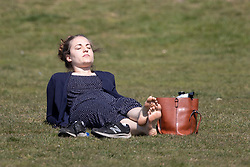 © Licensed to London News Pictures. 24/04/2021. London, UK. A woman relaxes during sunny weather in Greenwich Park in south east London. Temperatures are expected to rise with highs of 16 degrees forecasted for parts of London and South East England today . Photo credit: George Cracknell Wright/LNP