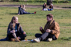 © Licensed to London News Pictures. 07/03/2021. London, UK. A couple in a bubble enjoy a picnic on Wimbledon common in the sunshine this afternoon. From Monday, 8th March 2021 two friends will be allowed to socialise out side of their household for a coffee or picnic for the first time in months. England will begin Stage1 of the easing of lockdown tomorrow, with children returning to school, care homes allowing a visitor and friends being allowed to socialise out side of their household. However, pubs, shops and restaurants will still remain closed. Photo credit: Alex Lentati/LNP