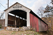 """Mecca Covered Bridge (150 feet long) was built in Burr Arch style over Big Raccoon Creek in 1873 by J.J. Daniels in historic Parke County, Indiana, USA. Red and white paint protects the wood. The traditional """"Cross this bridge at a walk"""" sign required slow vehicle speed, but traffic is now diverted to an adjacent modern bridge."""