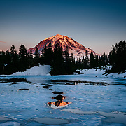 Summer ice covers the waters of Eunice Lake at sunset with Mount Rainier in Mount Rainier National Park.
