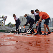 PARIS, FRANCE May 24.  Ground staff remove water from the covers of an outside court on a rainy day in Paris as they prepare the courts for the first day of the qualifying tournament at the 2021 French Open Tennis Tournament at Roland Garros on May 24th 2021 in Paris, France. (Photo by Tim Clayton/Corbis via Getty Images)