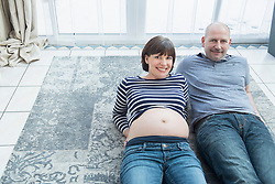 Portrait of couple lying on carpet at home