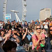 Audience on Westminster Bridge enjoying the various shows by comedians and troubadours. The Health and Care Bill has been passed by Parliament and is due to go to the House of Lords. In protest against the bill which aim to deconstruct and privatise large parts of the NHS UK Uncut activists together with health workers and trade unionists blocked the Westminster Bridge from 1pm til 5.30pm.
