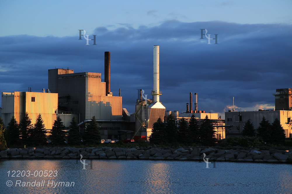Industrial buildings etched by sunrise overlook harbor in downtown Alpena, Michigan.