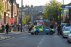 Queens Park, London,October 8th 2015. Police have cordoned off several roads as scene of crime detectives carry out their forensic investigation, following the shooting of a man allegedly armed with a knife, by officers after attempts to taser him failed. The shot man was taken to hospital. PICTURED: P0olice officers man the corons around the scene.  Contact: paul@pauldaveycreative.co.uk Mobile 07966 016 296