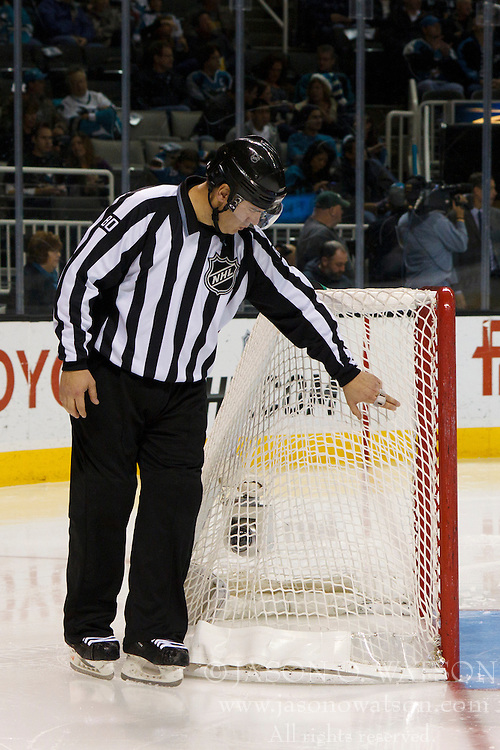 Dec 3, 2011; San Jose, CA, USA; NHL linesman Thor Nelson (80) inspects the netting on a goal before the start of the second period between the San Jose Sharks and the Florida Panthers at HP Pavilion. Florida defeated San Jose 5-3. Mandatory Credit: Jason O. Watson-US PRESSWIRE