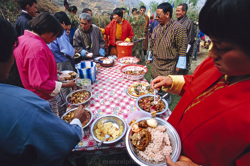 During a celebration of the first electricity to come to this region of Bhutan, visiting dignitaries join village member Namgay (at the head of the table) at a buffet of red rice, potatoes, tomatoes, cucumbers, beef, chicken, and a spicy cheese and chili pepper soup. The villagers have been stockpiling food for the event. (Supporting image from the project Hungry Planet: What the World Eats.) The Namgay family living in the remote mountain village of Shingkhey, Bhutan, is one of the thirty families featured, with a weeks' worth of food, in the book Hungry Planet: What the World Eats.