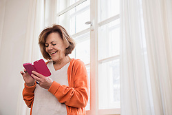 Happy senior woman text messaging on a smart phone by window, Munich, Bavaria, Germany