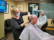 15 MAY 2020 - DES MOINES, IOWA: RHONDA STEWART, left, and BRUCE FULTON, barbers in Ferg's Barbershop in downtown Des Moines, wear face masks while they cut customers' hair for the first time in two months Friday.  The Governor of Iowa allowed most businesses in Iowa to reopen today, including barbershops, restaurants, coffee shops and malls. Restaurants are supposed to be working at 50% of normal capacity and barbershops are urged to take reservations and not allow customers to wait in the shop. Barbers are urged to wear face masks. Movie theaters, bars, museums, zoos, and casinons are still closed. On Friday, 15 May, Iowa reported 14,049 cases of COVID-19 and 336 deaths from disease since the start of the pandemic. Iowa's total number of infections continue to rise and several communities in Iowa have emerged as national hotspots for the spread of Coronavirus (SARS-CoV-2).         PHOTO BY JACK KURTZ