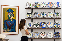 "© Licensed to London News Pictures. 01/09/2020. LONDON, UK. A staff member poses with (L to R) ""Femme assise (Dora Maar) [Seated Woman (Dora Maar)]"", 1955, and ""The Complete Set of 20 »Visage« plates"", 1963, all by Pablo Picasso.  Preview of ""Atelier Picasso"", a new exhibition recreating Pablo Picasso's studio in Cannes featuring his drawings, prints, ceramics and furniture.  The show is at Bastian gallery in Mayfair 3 September to 31 October 2020.  Visitors will be required to wear a facemask and practice social distancing.  Photo credit: Stephen Chung/LNP"