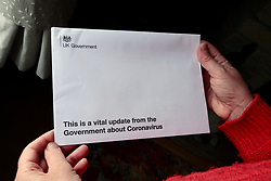 Covid 19 - Letter from  Prime Minister Boris Johnson to all UK households including a Government information leaflet on Coronavirus. UK April 2020. Posed by model