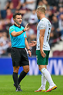 Referee Nick Walsh speaks with Ryan Porteous (#5) of Hibernian FC during the Cinch SPFL Premiership match between Heart of Midlothian and Hibernian at Tynecastle Park, Edinburgh, Scotland on 12 September 2021.