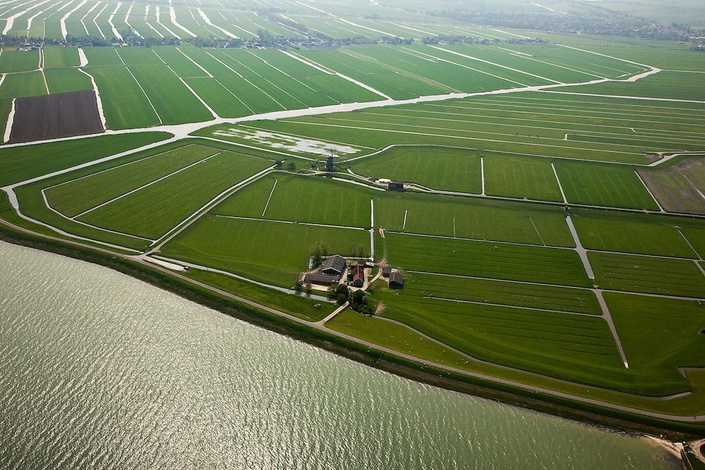 Nederland, Noord-Holland, Gemeente Zeevang, 28-04-2010; Polder de Zeevang met Polder de Etersheimerbraak (voorgrond). Deze laatste  polder is een voormalige 'braak' (dijkdoorbraak) die in 1632 bedijkt is (en vervolgens drooggemaakt). Tijdens de watersnood van 1916 stond het water aan de kruin van de Zeevangszeedijk (Zuiderzee- of IJsselmeerdijk). Om de dijk op te hogen - met klei, zijn in 1917 in de Etersheimerbraakpolder kleiputten gegraven (het gedeelte rechts van de boerderij). .Polder Zeevang with the Polder Etersheimerbraak. This polder is a former 'breach' (levee failure) that was diked in 1632 (and subsequently dried). During the flood of 1916, the water stood at the top of the Zeevang seawall. To raise the top of the seawall, clay was needed and in 1917 clay pits were dug in the Etersheimerbraakpolder (the part to the right of the farm)..luchtfoto (toeslag), aerial photo (additional fee required).foto/photo Siebe Swart