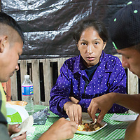 Migrants share from a single plate on the way from Huixtla to Pijijiapan