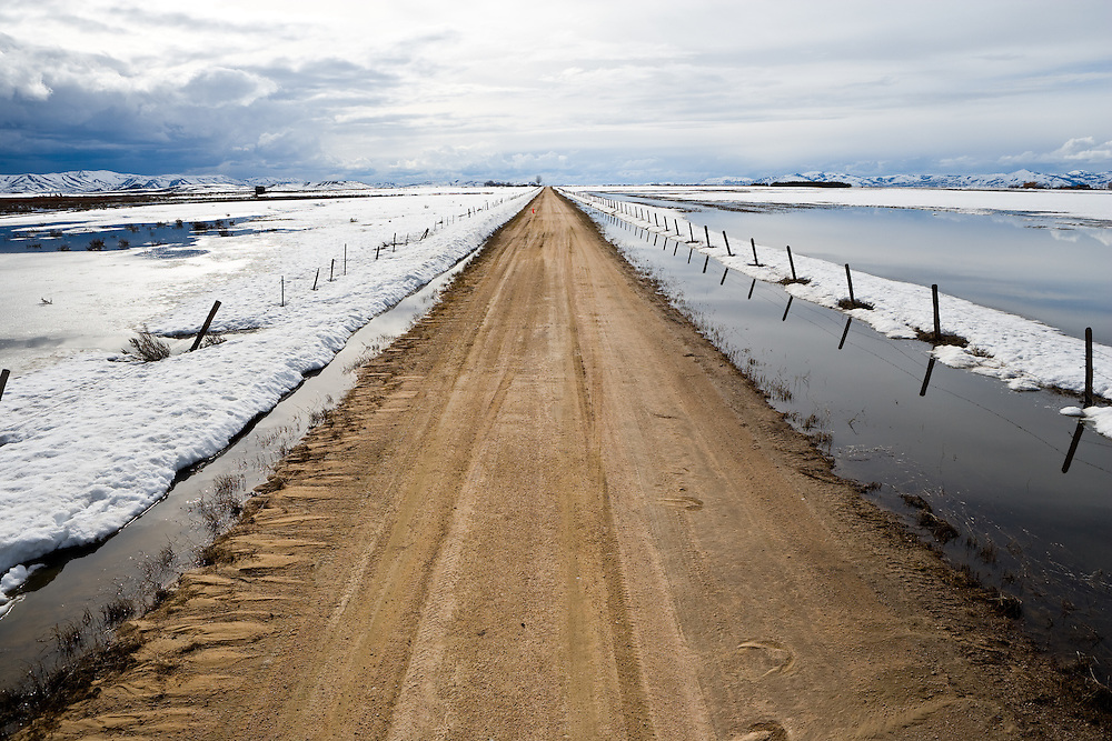 Spring snow melt on the Camas Prairie in Southwest Idaho contrast against a recently flooded dirt road. Editions of 17