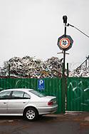 parked BMW in front of the premises of a scrap yard with old metal in the district Deutz, Cologne, Germany.<br /> <br /> geparkter BMW vor dem Gelaende eines Schrottplatzes mit Altmetall im Stadtteil Deutz, Koeln, Deutschland.