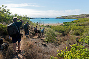Tourists exploring the island of Santa Fe, Galapagos. In the background is the beautiful Barrington Bay, a common landing site oin the island.