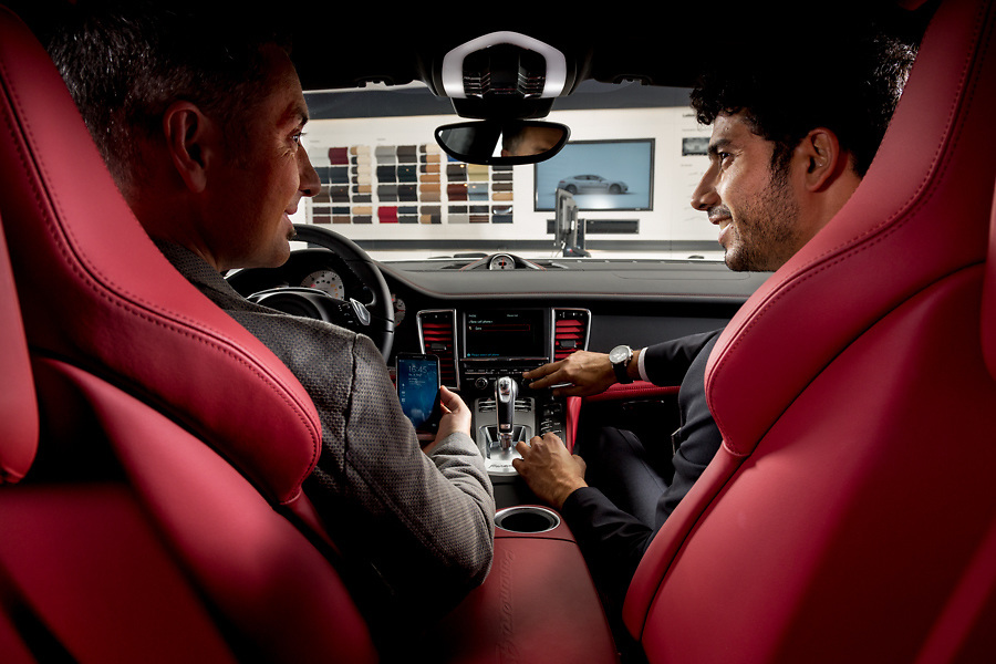 Two men talking in a special porsche car about the interior