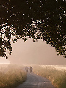 Walkers stroll down a track in rural countryside in Umbria on a misty morning, under a hilltop town near Solomeo in Italy