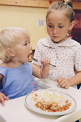 Toddler eating lunch with girl standing next to her at surviving homelessness project,