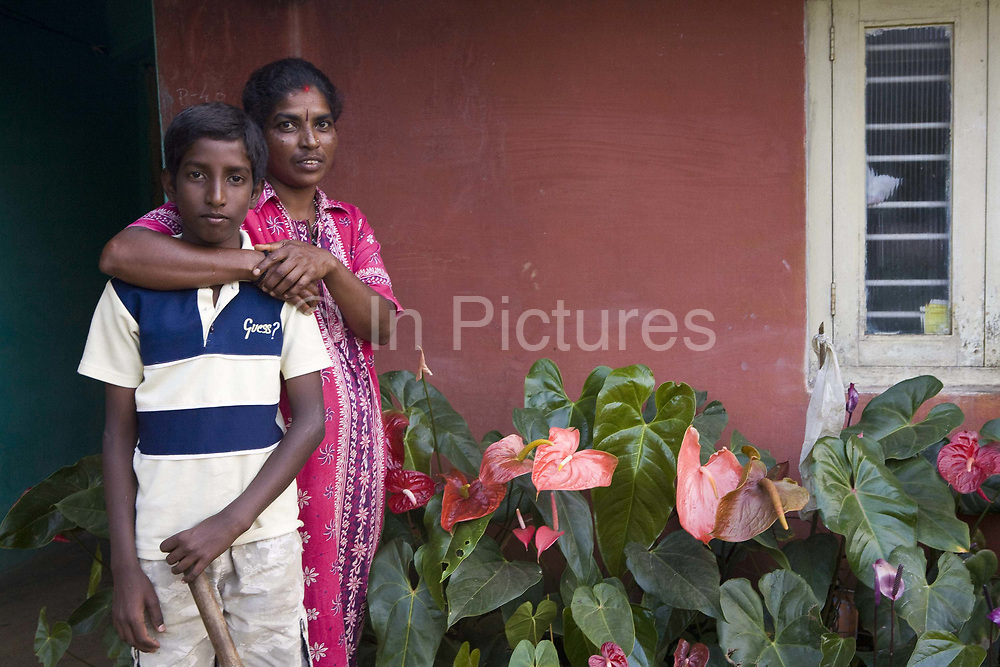 Woman and her son outside their house. Coorg or Kadagu is the largest coffee growing region of India, in the state of Karnataka, the inhabitants - the Kodavas have been cultivating crops such as coffee, black pepper and cardamon for many generations.