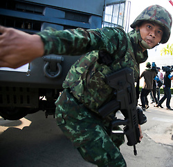 © Licensed to London News Pictures. 22/05/2014. An armed Thai military officer tells media to move back as they block the entrance to the Army club during a meeting hosted by Thailand's army chief at the Army Club, between representatives from both sides of the country's political groups the PDRC & UDD at the conclusion of the meeting the Thailand army imposed a Military Coup, in Bangkok Thailand.  Photo credit : Asanka Brendon Ratnayake/LNP