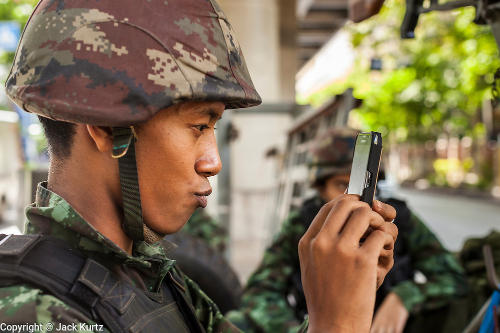 """20 MAY 2104 - BANGKOK, THAILAND: A Thai soldier takes a """"selfie"""" at a checkpoint on Rama I Road in Bangkok. The Thai Army declared martial law throughout Thailand in response to growing political tensions between anti-government protests led by Suthep Thaugsuban and pro-government protests led by the """"Red Shirts"""" who support ousted Prime Minister Yingluck Shinawatra. Despite the declaration of martial law, daily life went on in Bangkok in a normal fashion. There were small isolated protests against martial law, which some Thais called a coup, but there was no violence.   PHOTO BY JACK KURTZ"""