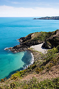 View down towards Vicard harbour, a secluded pebbly bay, surrounded by crystal clear calm turquoise water on the North Coast of  Jersey, CI