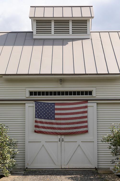 The American Flag draped across a barn doorway in Woodstock Vermont.