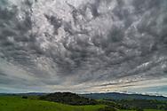 Stratocumulus stratiformis opacus undulatus clouds beneath cirrostratus clouds over Briones Regional Park, California