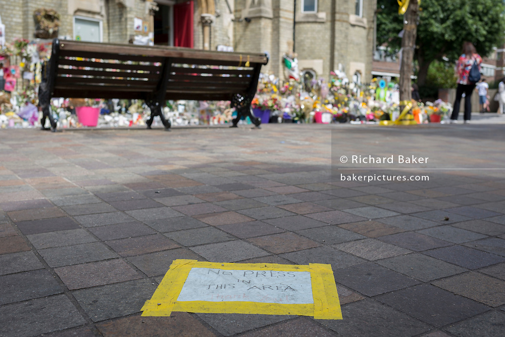 Twelve days after the devastating fire that killed an unspecified number of people in Grenfell Tower, yellow tape marks where the local community urged the media to keep back from a shrine of flowers, on 26th June 2017, in the London borough of Kensington & Chelsea, England.