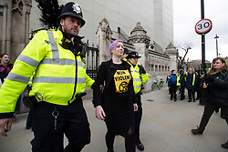 © Licensed to London News Pictures. 26/02/2020. London, UK. Extinction Rebellion protesters are led away by police after they sprayed plant based fake oil on the hoarding surrounding Big Ben . Photo credit: George Cracknell Wright/LNP