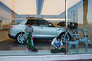 Shop workers setting up Christmas decorations in a Range Rover showroom on 10-13 Sino Plaza, Gloucester Road, Causeway Bay, Hong Kong.