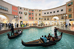 Gondola boat trips on indoor canal at Italian themed Villaggio Shopping Mall in Doha Qatar