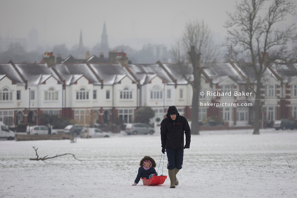 An adult pulls a child uphill on a small sledge in Ruskin Park, south London during the bad weather covering every part of the UK and known as the 'Beast from the East' because Siberian winds and very low temperatures have blown across western Europe from Russia, on 1st March 2018, in Lambeth, London, England.